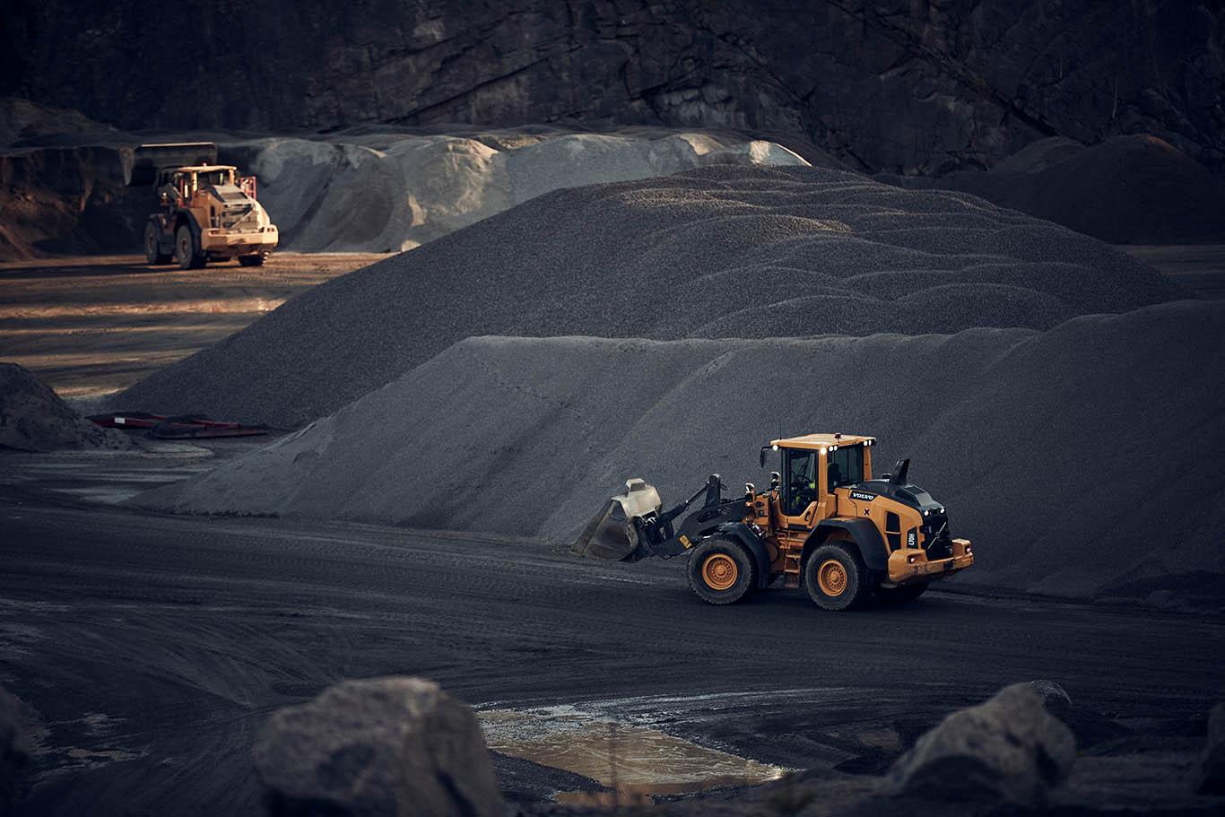 Två grävmaskiner i en bergtäckt